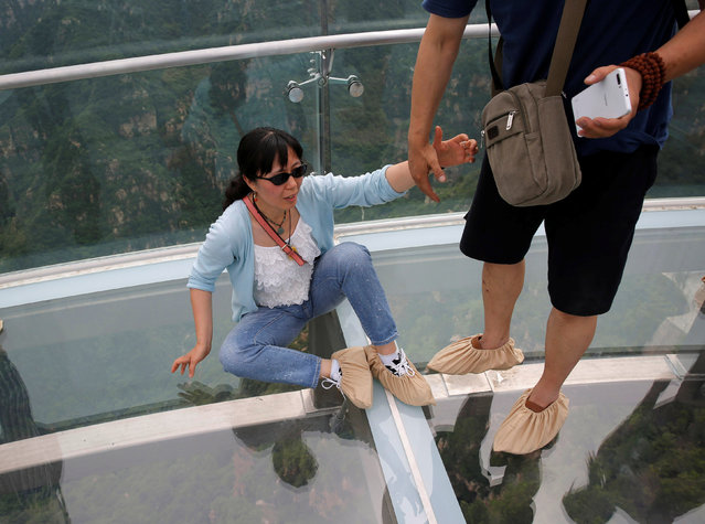 A woman is helped by a man as she tries to stand up on glass floor of the glass sightseeing platform on Shilin Gorge in Beijing, China, May 27, 2016. (Photo by Kim Kyung-Hoon/Reuters)