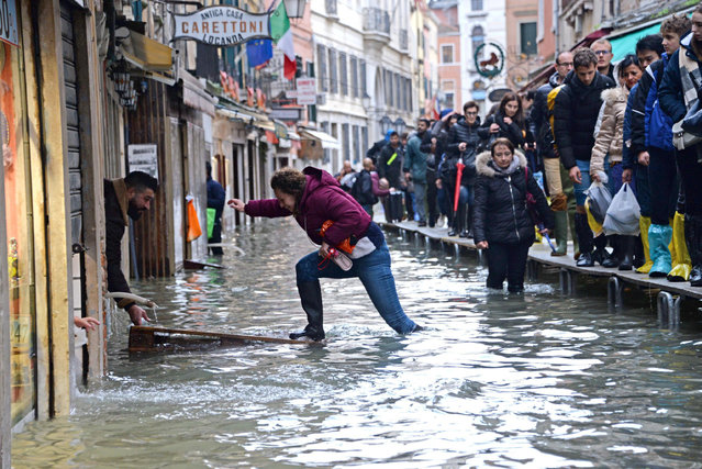 A woman tries to cross a flooded street as people walk on a trestle bridge during high water, in Venice, northern Italy, Friday, November 15, 2019. Exceptionally high tidal waters returned to Venice on Friday, prompting the mayor to close the iconic St. Mark's Square and call for donations to repair the Italian lagoon city just three days after it experienced its worst flooding in 50 years. (Photo by Andrea Merola/ANSA via AP Photo)