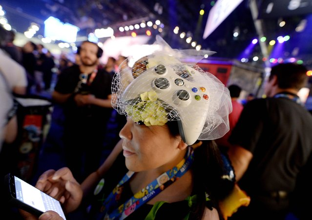 "Microsoft employee Sammy Ng wears an Xbox game controller as a fascinator as she watches a trailer of the new multiplayer action game ""Call of Duty: Advanced Warfare"" in the Activision booth at the 2014 Electronic Entertainment Expo, known as E3, in Los Angeles, June 10, 2014.  REUTERS/Kevork Djansezian"