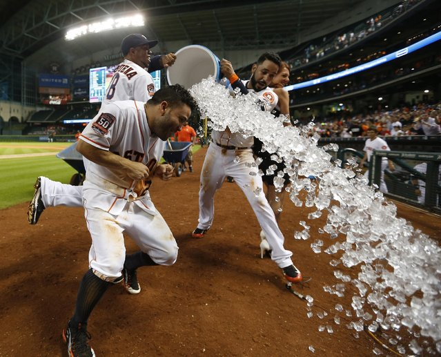Houston Astros' Jose Altuve (27) gets dunked by Luis Valbuena (18) and Marwin Gonzalez, right, after hitting the game-winning home run in the ninth inning of a baseball game against the Boston Red Sox at Minute Maid Park on Thursday, July 23, 2015, in Houston. The Astros won 5-4. (Photo by Karen Warren/Houston Chronicle via AP Photo)