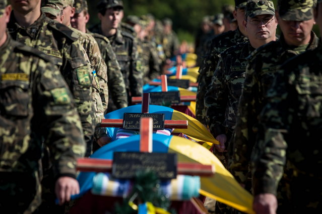 Funeral ceremony for unidentified soldiers at the Kushugum cemetery in Zaporozhye, Ukraine on October 2, 2014. Presumably, these are the bodies of servicemen from the 93rd, 51st, 24th brigades and the Donbass battalion who died at the entrance of the military conflict in the southeast of the country near Ilovaisk. (Photo by Konstantin Sazonchik/TASS)