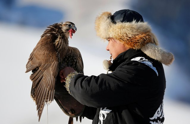 A hunter holds his tamed hawk during a traditional hunting contest outside the village of Kaynar in Almaty region, Kazakhstan on December 8, 2019. (Photo by Pavel Mikheyev/Reuters)