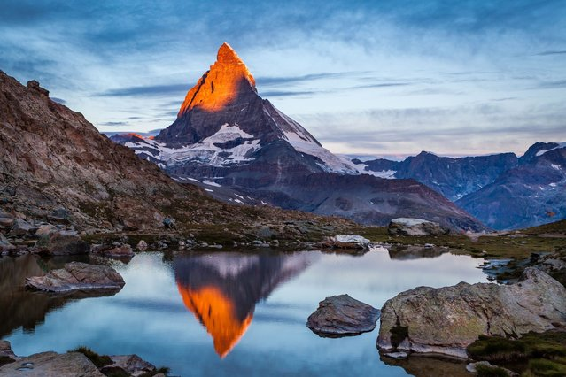 The summit of one of Europe's tallest mountains glows like the flame of a candle as the sun rises on a clear morning. The Matterhorn, famous for appearing on bars of Toblerone chocolate bars, reflects the vivid orange light at 5.37am. (Photo by Margarethe Jaeger/Solent News & Photo Agency)