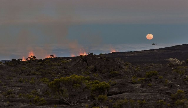 The moon rises as molten lava erupts from the Piton de la Fournaise, one of the world's most active volcanoes, in this picture taken July 31, 2015, on the French Indian Ocean Reunion Island. (Photo by Gilles Adt/Reuters)
