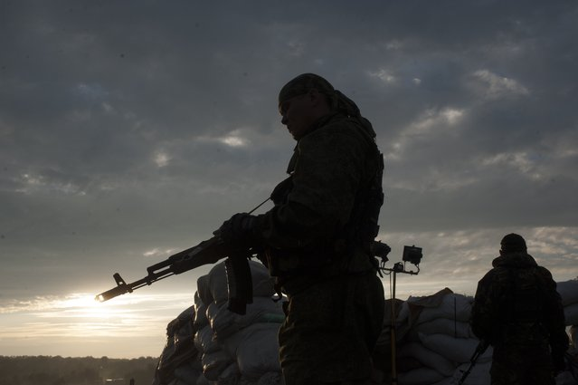 Pro-Russian fighters stand guard at a check point in the village of Karlivka near Donetsk, eastern Ukraine, Wednesday, June 18, 2014, during a handover of the bodies of Ukrainian troops who died in a plane shot down near Luhansk. The two sides managed to arrange a brief truce Wednesday evening in the eastern town of Karlivka to allow pro-Russian forces to hand over the bodies of 49 Ukrainian troops who died when the separatists shot down a transport plane bound for the airport in Luhansk last weekend. (Photo by Evgeniy Maloletka/AP Photo)