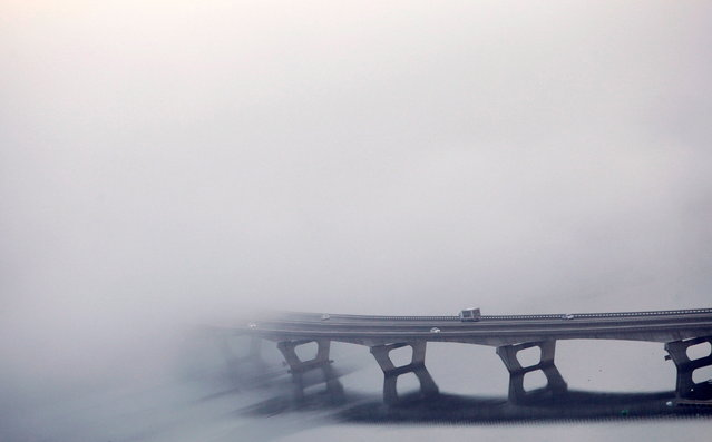 Fog covers the AP-9 bridge in Cabanas, Galicia, northwestern Spain, 22 October 2019. Warnings for heavy rain have been issued in various regions in the Spanish territory. (Photo by EPA/Cabalar)