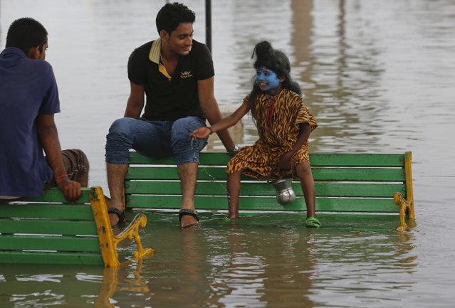 An Indian boy dressed as Hindu god Shiva to attract alms from devotees chats with tourists as they sit on benches partially submerged in flood waters on the banks of the River Ganges in Allahabad, India, Thursday, July 30, 2015. The Ganges, one of India's largest rivers is flooded following monsoon rains. (Photo by Rajesh Kumar Singh/AP Photo)
