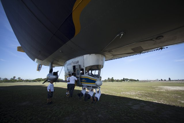 """Grounds crew prepare to load passengers into the Goodyear blimp """"Spirit of America"""" in Carson, California August 5, 2015. (Photo by Mike Blake/Reuters)"""