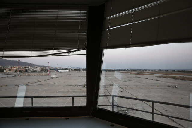 A plane is seen through the window of an auxiliary control tower at the former Athens International airport, Hellenikon June 16, 2014. (Photo by Yorgos Karahalis/Reuters)
