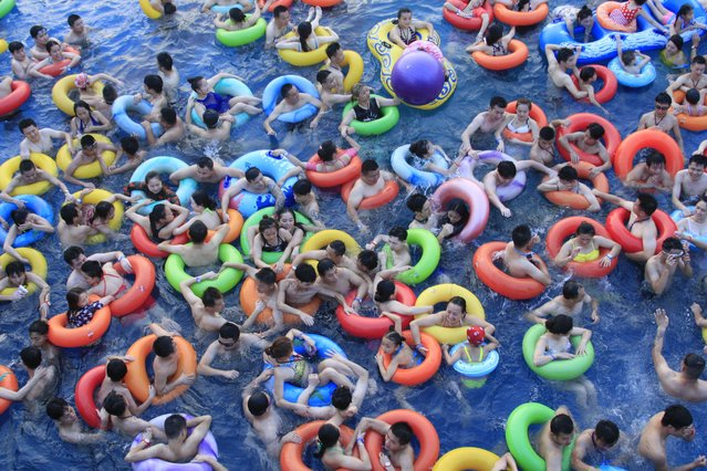 Chinese holidaymakers crowd a swimming pool at a water park in Nanchang city, east China's Jiangxi province, 16 July 2017. (Photo by Imaginechina/Rex Features/Shutterstock)