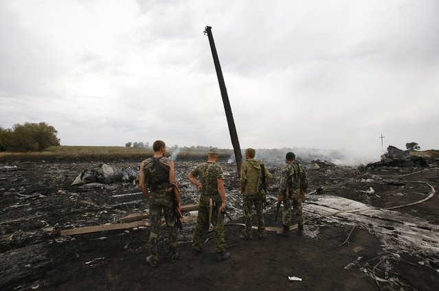 Armed pro-Russian separatists stand at the site of a Malaysia Airlines Boeing 777 plane crash near the settlement of Grabovo in the Donetsk region, July 17, 2014. The Malaysian airliner Flight MH-17 was brought down over eastern Ukraine on Thursday, killing all 295 people aboard and sharply raising the stakes in a conflict between Kiev and pro-Moscow rebels in which Russia and the West back opposing sides. (Photo by Maxim Zmeyev/Reuters)