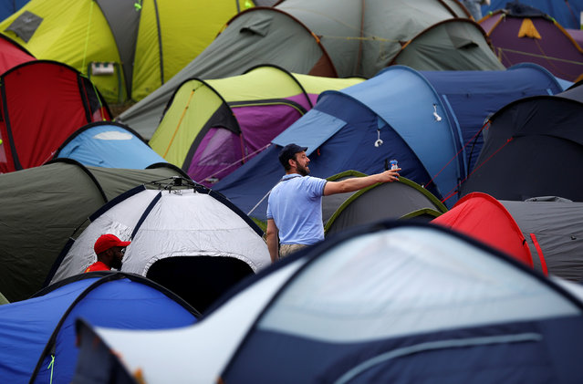 Revellers stand near tents during the Glastonbury Festival at Worthy Farm in Somerset, Britain, June 23, 2016. (Photo by Stoyan Nenov/Reuters)