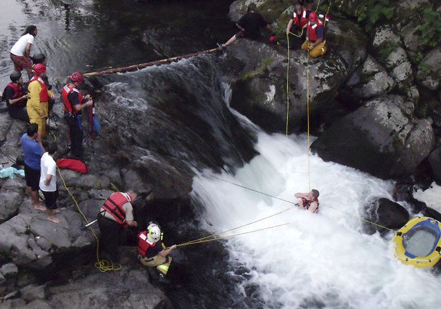 In this July 14, 2014 photo released by the Skamania County Sheriff's Office, Skamania County sheriff's deputies and firefighters rescue John Napierkowski, bottom right, who was trapped in the water at Dougan Falls on the Washougal River in Washougal, Wash. Napierkowski was taken to a hospital after he was trapped in the cold water for about an hour. (Photo by AP Photo/Skamania County Sheriff's Office)