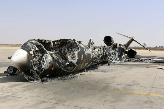 A wreckage of a burnt aircraft is pictured after a shelling at Tripoli International Airport July 21, 2014. Heavy fighting erupted on Sunday around Tripoli International Airport, where rival militias have been battling for control, killing at least four people and forcing thousands from their homes, local residents and witnesses said. (Photo by Hani Amara/Reuters)