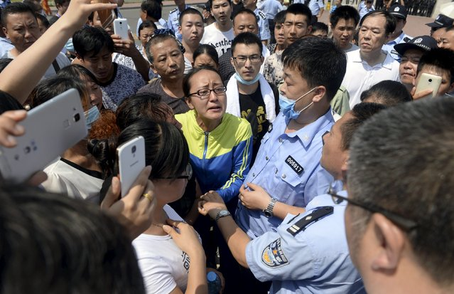 A woman speaks to a government official (bottom R wearing glasses), near policemen during a protest to demand information about those missing following Wednesday's blasts, mostly firefighters, in front of the Binhai new district government building, in Tianjin, China, August 16, 2015. Chinese soldiers and rescue workers in gas masks and hazard suits searched for toxic materials in China's port of Tianjin on Sunday as Premier Li Keqiang arrived to offer condolences, days after explosions flattened part of a national development zone. (Photo by Reuters/Stringer)
