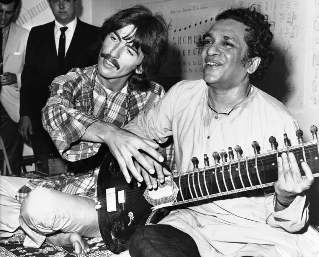 "George Harrison of the Beatles sits cross-legged with his musical mentor, Ravi Shankar of India, a sitar virtuoso, in Los Angeles, August 3, 1967, as Harrison explains to newsmen that Shankar is teaching him to play the sitar, a 25-stringed guitar-like instrument. Harrison said ""Indian music makes God come through in a spiritual way"". (Photo by AP Photo)"