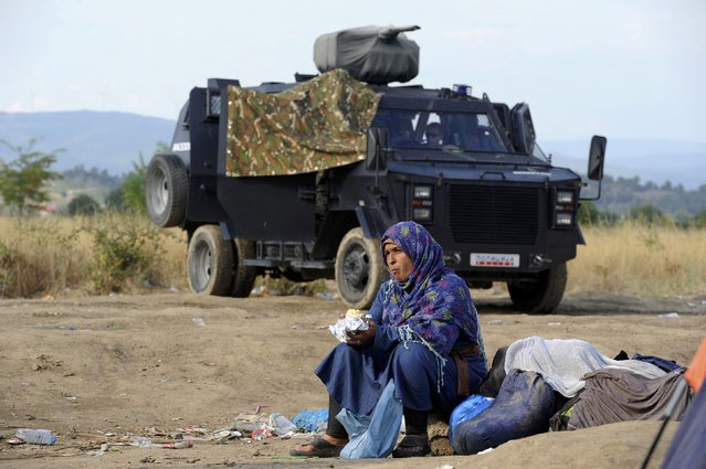 A migrant woman eats as a Macedonian police vehicle is seen in the background near the village of Idomeni at the Greek-Macedonian border, August 20, 2015. Macedonia moved to cut off the flow of migrants pouring over its southern border with Greece on Thursday, deploying riot police in armored vehicles and calling out the army under a state of emergency. (Photo by Alexandros Avramidis/Reuters)