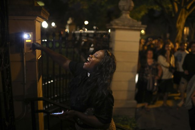 A woman rings the doorbell at the gate of the Governors Mansion as demonstrators gather in St. Paul, Minn.,  protesting a police involved shooting early Thursday, July 7, 2016. A Minnesota officer fatally shot a man in a car with a woman and a child in Falcon Heights,  an official said.  St. Anthony Police interim police chief Jon Mangseth said the incident began when an officer pulled over a vehicle Wednesday in the St. Paul suburb. Mangseth said he did not have details about the reason for the traffic stop, but that at some point shots were fired. The man was struck but no one else was injured, he said. (Photo by Jeff Wheeler/Star Tribune via AP Photo)
