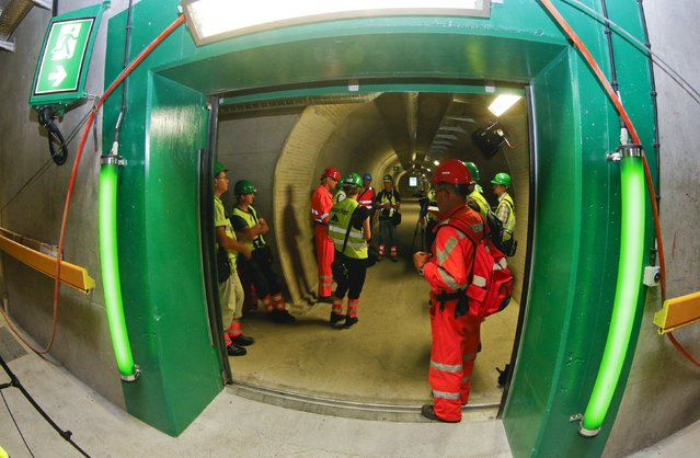Journalists listen to explanations as they stand in an emergency tunnel at a multifunction and emergency stop station of the NEAT Gotthard Base Tunnel during a media visit near the town of Sedrun August 24, 2015. (Photo by Arnd Wiegmann/Reuters)