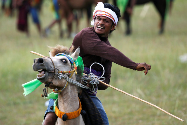 """A Sumbanese man reacts as he throws a javelin during Pasola """"war"""" festival, an annual ancient ritual to welcome the new harvest season as they ask for God's blessings for a good harvest which believed could increase their crops for the further years by riding horses and trying to hit each other with javelins, in Lamboya district, West Sumba, East Nusa Tenggara province, Indonesia, February 20, 2020. (Photo by Willy Kurniawan/Reuters)"""