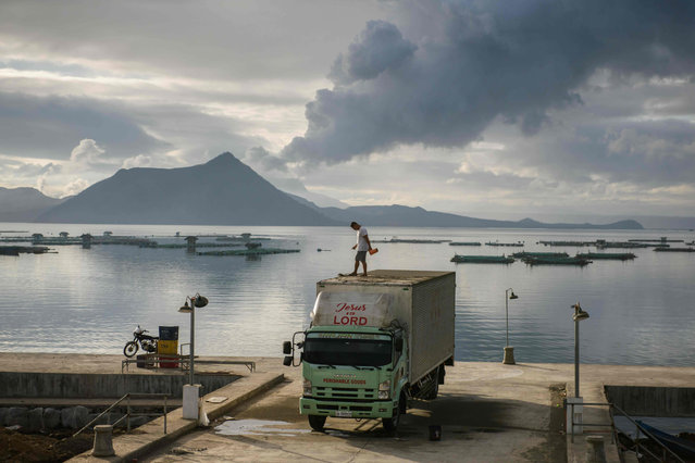 A man clears ash from the roof of his truck, before a plume of steam rising from the Taal volcano, at a fishing harbour in Laurel on January 17, 2020. (Photo by Ed Jones/AFP Photo)