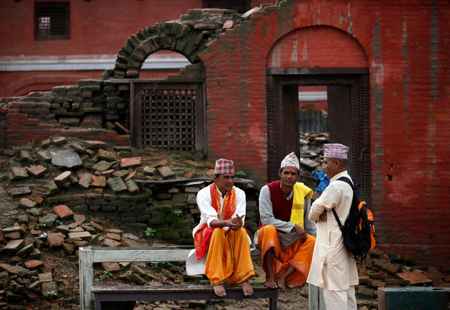 Hindu priests rest near the building damaged during last year's earthquake at the Pashupatinath temple during the Shrawan Sombar festival in Kathmandu, Nepal, July 18, 2016. The festival lasts for a month, during which devotees fast and worship Lord Shiva to pray for happiness for their families. (Photo by Navesh Chitrakar/Reuters)