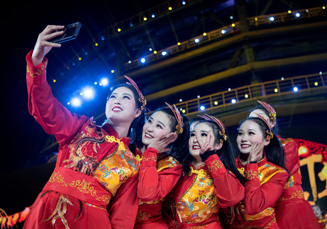 Performers take photos after the new year count down celebration at the Shougang Industrial Park, Shijingshan District, in Beijing on January 1, 2020. Later that day a seafood market in Wuhan – some 1,100 kilometers south of Beijing – was shut down after several customers were reported to be suffering from a mysterious disease. Since then the strain of coronavirus known as COVID-19 has killed 3,270 people in China. (Photo by Noel Celis/AFP Photo)