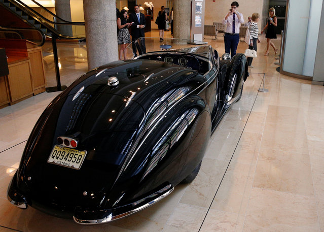 "People look at a 1939 Alfa Romeo 8C 2900B Lungo Touring Spider displayed at Sotheby's in New York City, New York, U.S. July 21, 2016. The car, unveiled in a pre-publicity showing in New York on Thursday, is expected to sell for more than US$15 million – and could set a record for the most money ever paid for a pre-war auto at auction. ""This is a personal favourite of mine, the 1939 Alfa Romeo is one of the grandest pre-war cars ever built"", said Ian Kelleher, managing director, RM Sotheby's US West Coast division. ""You can achieve speeds in excess of 100 miles an hour in this car. (Photo by Brendan McDermid/Reuters)"