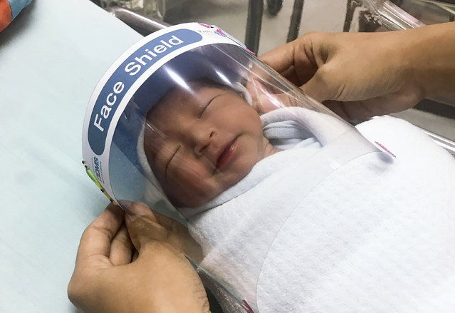 In this Friday, April 3, 2020, photo released by Paolo Hospital Samutprakarn, a nurse adjusts tiny face shield for a newborn baby to protect from new coronavirus at the newborn nursery of the hospital in Samutprakarn province, central Thailand. (Photo by Paolo Hospital Samutprakarn via AP Photo)