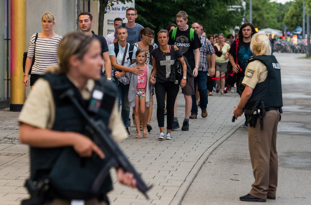 Police officers escort people from inside the shopping center as they respond to a shooting at the Olympia Einkaufzentrum (OEZ) at July 22, 2016 in Munich, Germany. According to reports, several people have been killed and an unknown number injured in a shooting at a shopping centre in the north-western Moosach district in Munich. Police are hunting the attacker or attackers who are thought to be still at large. (Photo by Joerg Koch/Getty Images)