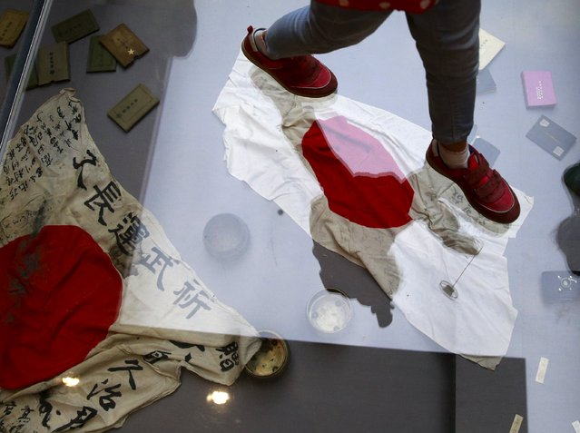 A visitor walks on a glass flooring above Japanese military flags seized by the Chinese People's Liberation Army (PLA) during World War Two, at the Museum of the War of Chinese People's Resistance Against Japanese Aggression, in Beijing, China, September 1, 2015, two days ahead of the commemoration of the 70th anniversary of the end of World War Two. Some 12,000 soldiers will march through Beijing's central Tiananmen Square on Thursday. (Photo by Kim Kyung-Hoon/Reuters)