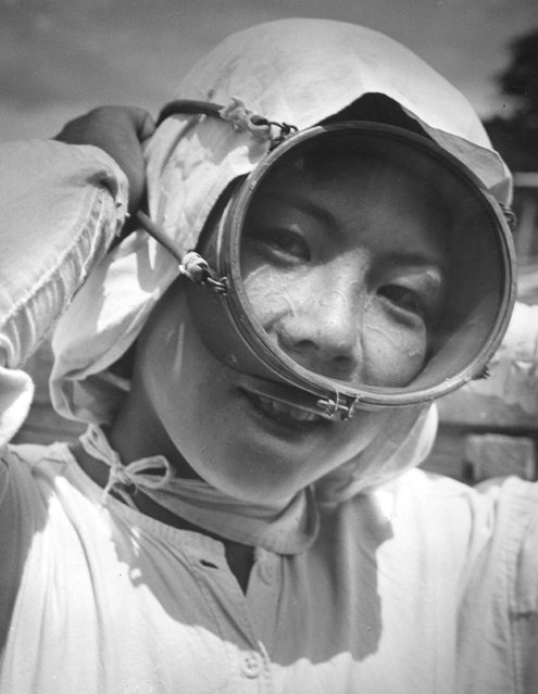 """A young Japanese girl adjusts her face mask before another dive, May 1956. Known as an """"Ama"""", she will dive all day long catching shellfish. (Photo by Keystone Features)"""