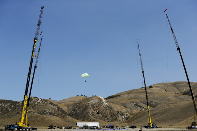 In this Monday, July 25, 2016 photo, skydiver Luke Aikins, center, descends on a parachute as production crew members set up a net about one-third the size of a football field and 20 stories high on the ground in Simi Valley, Calif. (Photo by Jae C. Hong/AP Photo)