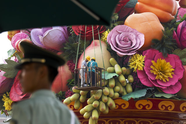 A Chinese paramilitary policeman stands watch as workers put finishing touch on a giant basket decorated with replicas of flowers and fruits on display at Tiananmen Square in Beijing, Monday, September 25, 2017. (Photo by Andy Wong/AP Photo)