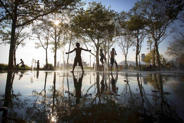 Children play in a fountain in the late afternoon sun in the Lower Manhattan borough of New York August 25, 2014. (Photo by Carlo Allegri/Reuters)