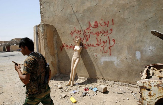A Kurdish Peshmerga fighter walks past a mannequin leaning on the wall of the former headquarters of Islamic State militants in Sulaiman Pek, after the town was recaptured this week, September 3, 2014. (Photo by Ahmed Jadallah/Reuters)