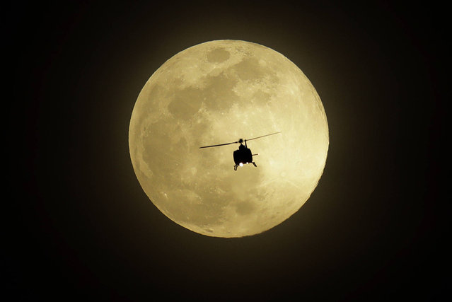 A helicopter flies in front of a full moon Monday, April 10, 2017, in Las Vegas. (Photo by John Locher/AP Photo)