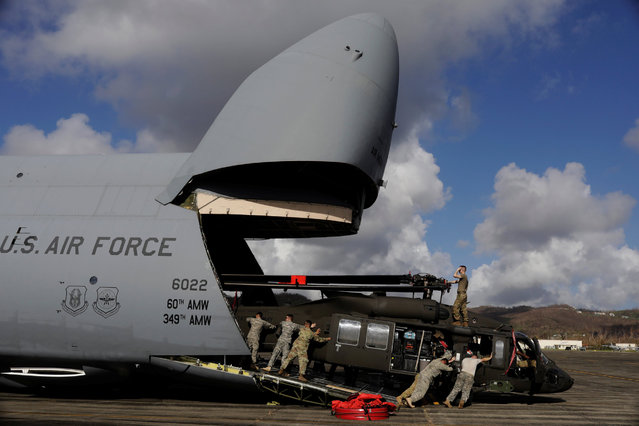 Soldiers with the U.S. Army's 1st Armored Division, Combat Aviation Brigade, work to unload a UH-60 Blackhawk helicopter from a U.S. Air Force C-5 Galaxy to aid in recovery efforts following Hurricane Maria in Roosevelt Roads, Puerto Rico, October 4, 2017. (Photo by Lucas Jackson/Reuters)
