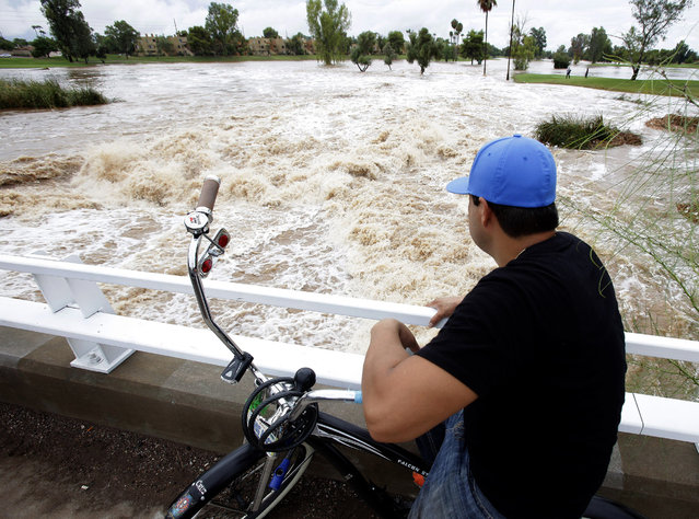 A man watches floodwaters surge under an overpass Monday, September 8, 2014, in Scottsdale, Ariz. The remnants of Hurricane Norbert pushed into the desert Southwest and swamped Arizona Monday, breaking the previous record for rainfall in a single day in Phoenix. (Photo by Rick Scuteri/AP Photo)