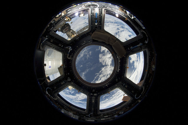 A view of Earth from the Cupola on the earth-facing side of the International Space Station, June 12, 2013. Visible in the top left foreground is a Russian Soyuz crew capsule. In the lower right corner, a solar array panel can be seen. (Photo by Reuters/NASA)