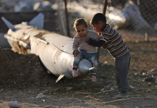 A Syrian boy places another child on the tip of an abandoned missile at the Ash'ari camp for the displaced in the rebel-held eastern Ghouta area outside the capital Damascus on October 25, 2017. (Photo by Amer Almohibany/AFP Photo)