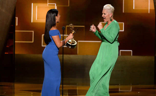 "Gina Rodriguez, left, presents the award for outstanding makeup for a limited series or a movie (non-prosthetic) to Eryn Krueger Mekash for ""American Horror Story: Freak Show"" at the Television Academy's Creative Arts Emmy Awards at Microsoft Theater on Saturday, September 12, 2015, in Los Angeles. (Photo by Phil McCarten/Invision for the Television Academy/AP Images)"