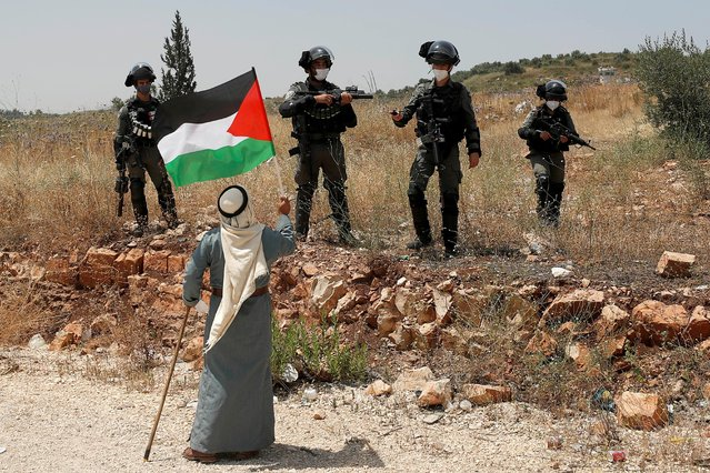 A demonstrator holds a Palestinian flag in front of Israeli forces during a protest against Israel's plan to annex parts of the occupied West Bank, near Tulkarm on June 5, 2020. (Photo by Mohamad Torokman/Reuters)