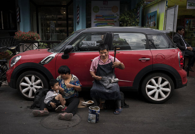 A blind Chinese man plays traditonal music as his wife and child sit next to him while begging for change in the street at an outdoor shopping district on September 12, 2014 in Beijing, China. (Photo by Kevin Frayer/Getty Images)