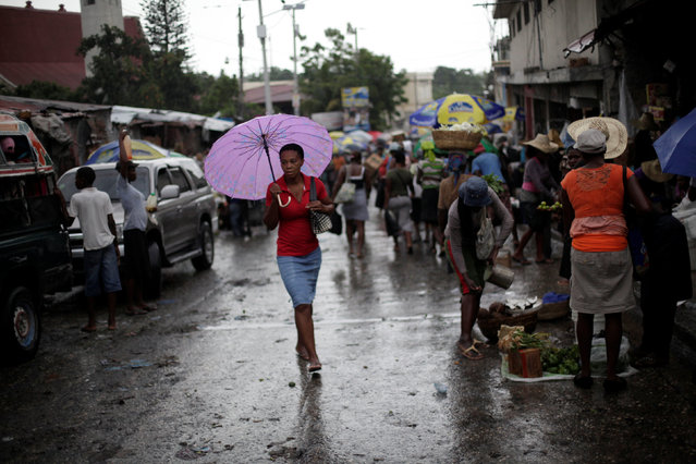 A woman walks with an umbrella in Port-au-Prince, Haiti, August 10, 2016. (Photo by Andres Martinez Casares/Reuters)