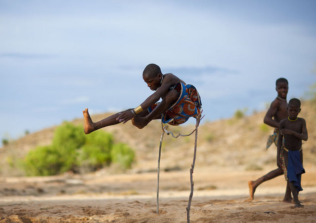 """Mucubal kid jumping – Angola. In Mucubal tribe, when you live in the bush, no PSP, no WII, no TV, no Radio..so the game the kids like the most is to jump over a wood hurdle. They have to touch a stone in front of the hurdle before jumping.