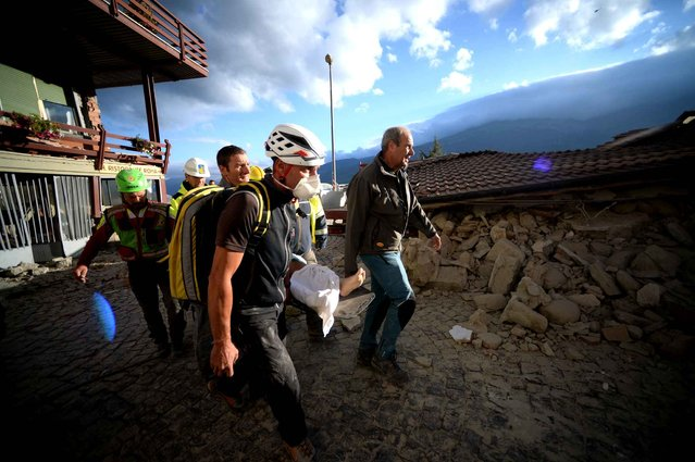 Rescuers carry an injured man among damaged homes after a strong heathquake hit Amatrice on August 24, 2016. (Photo by Filippo Monteforte/AFP Photo)