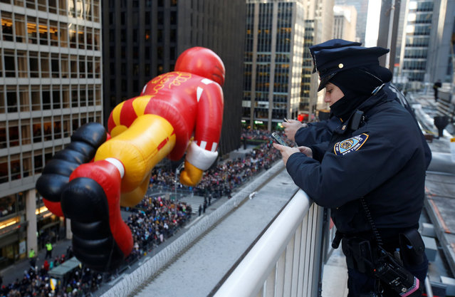New York City Police Department officers watch the Ronald McDonald balloon make its way down 6th Ave during the 91st Macy's Thanksgiving Day Parade in the Manhattan borough of New York City, The  York, U.S., November 23, 2017. (Photo by Carlo Allegri/Reuters)