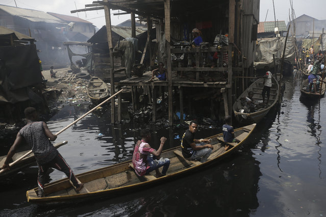 People travel by canoe in the floating slum of Makoko in Lagos, Nigeria, Saturday March 21, 2020. Lockdowns have begun in Africa as coronavirus cases rise above 1,000, while Nigeria on Saturday announced it is closing airports to all incoming international flights for one month in the continent's most populous country. Concerns are mounting for the welfare of Nigeria's most vulnerable community on stilts over spread of Covid-19 with little or no chances for social distancing as confirmed positive cases of the disease is on the rise. (Photo by Sunday Alamba/AP Photo)