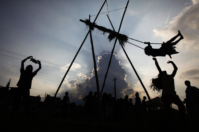 A Nepalese girl riding a swing and a boy flying a kite, left are silhouetted against the sky during the Dashain festival in Katmandu, Nepal, Monday, September 29, 2014. Dashain commemorates the victory of the Hindu gods and goddesses over demons and of the victory of good over evil. (Photo by Niranjan Shrestha/AP Photo)